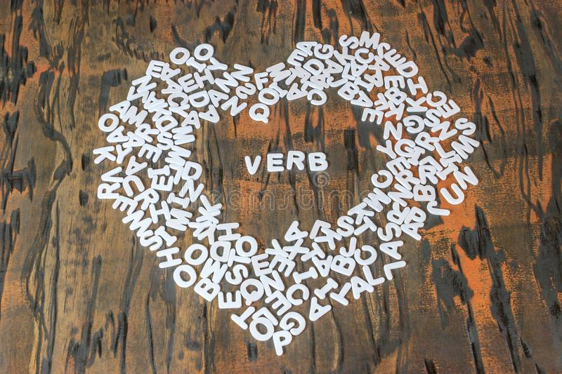 Word verb inside heart. Made of white letters stock photos
