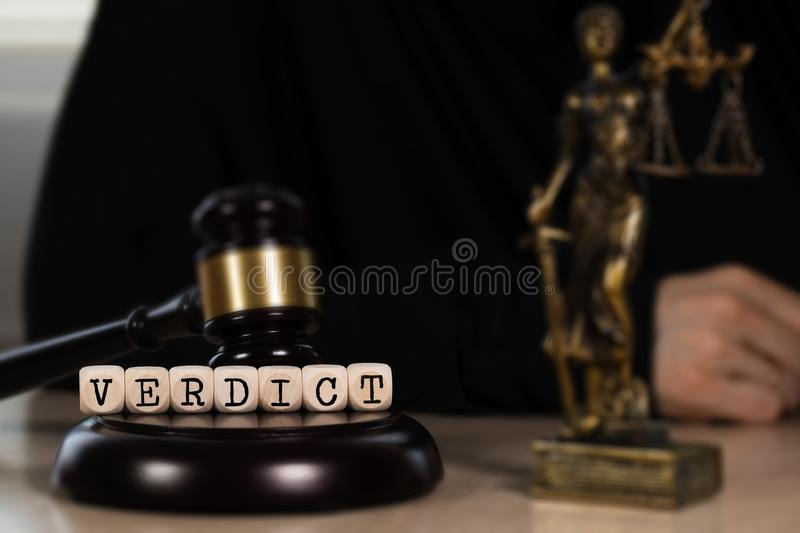 Word VERDICT composed of wooden dices. Wooden gavel and statue of Themis in the background. Word VERDICT  composed of wooden dices. Wooden gavel and statue of royalty free stock photography