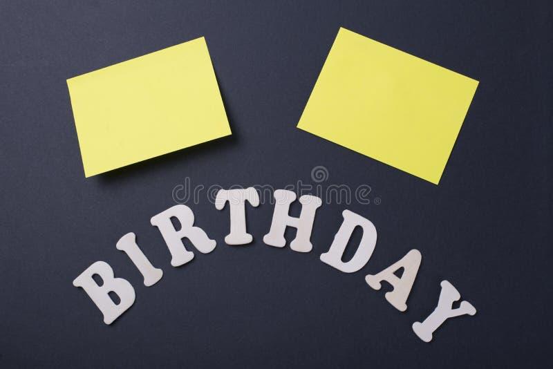 Word Verjaardag naast twee gele post-its op zwarte achtergrond royalty-vrije stock fotografie