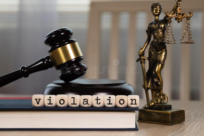 Word VIOLATION composed of wooden dices. Wooden gavel and statue of Themis in the background royalty free stock photography