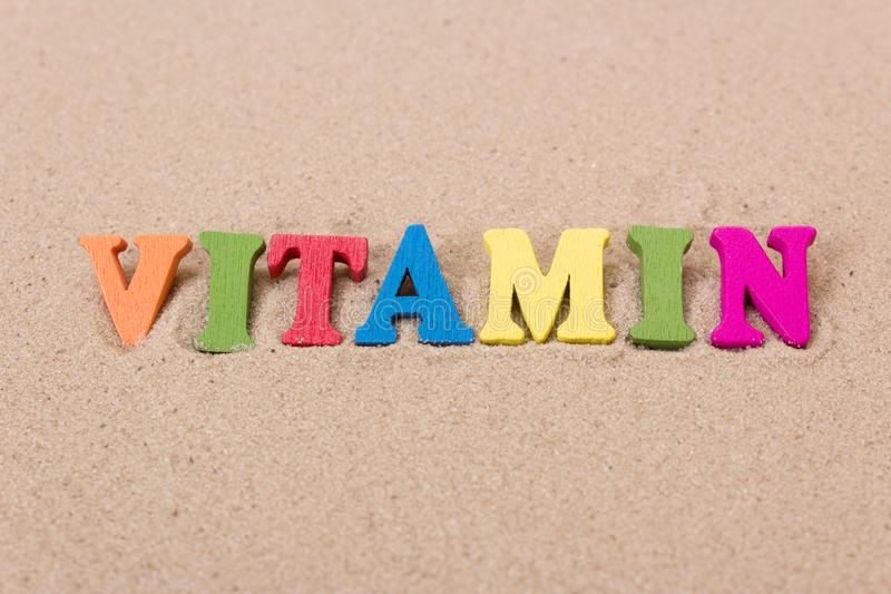 Word vitamin D of colored wooden letters on sandy beach stock photos