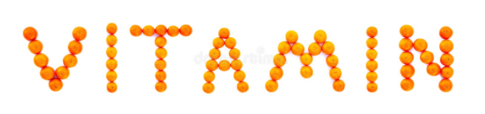 Word Vitamin folded from tangerines isolated on white background royalty free stock photo