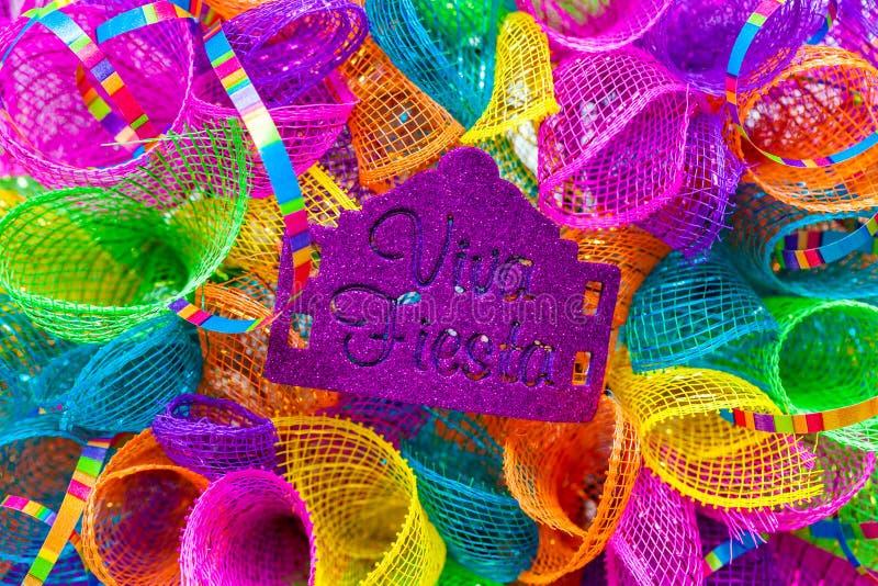 The word `viva fiesta` written in purple glitter on multicolored mash stock photo