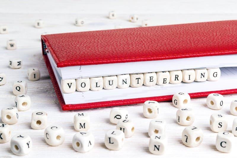 Word Volunteering written in wooden blocks in red notebook on wh stock photos