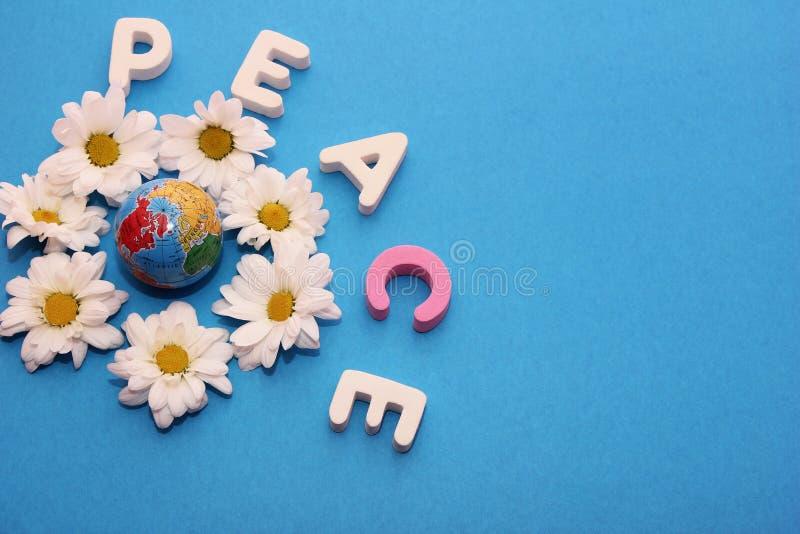 Word VREDE per brieven dichtbij weinig die cijfer van een bol wordt door bloemen van witte chrysanten wordt omringd gemaakt die D royalty-vrije stock fotografie