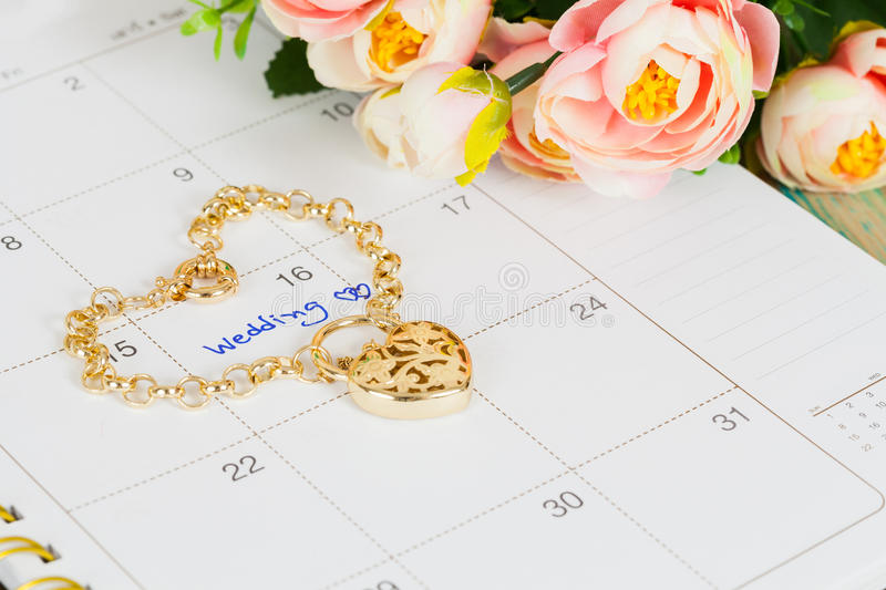 Word wedding on calendar and gold bracelet royalty free stock photography