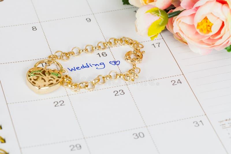 Word wedding on calendar and gold bracelet stock images