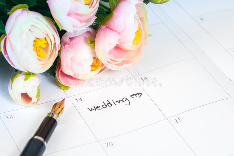 Word wedding on calendar with sweet flowers and pen royalty free stock images