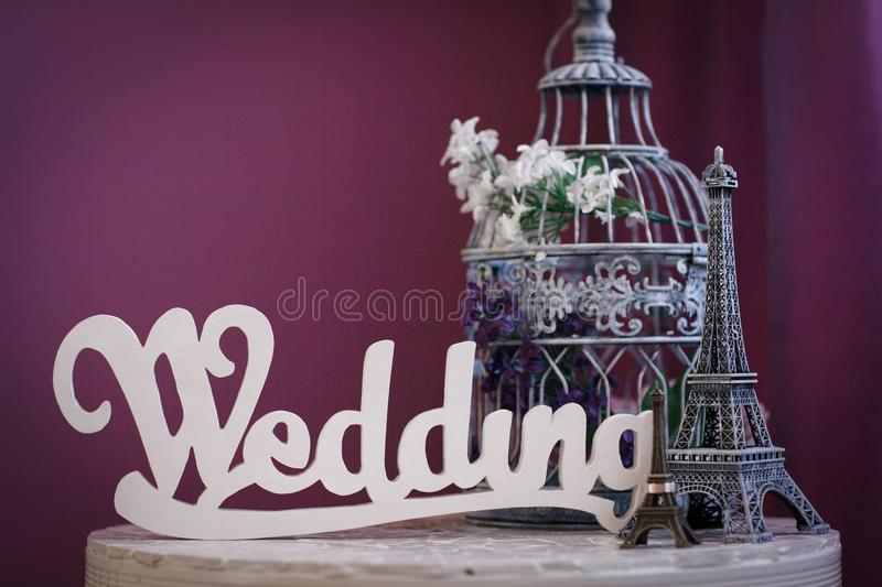 Word `Wedding` made of white wooden letters, statuettes of Eiffel Tower, and cage for birds, stand on table on purple background royalty free stock images