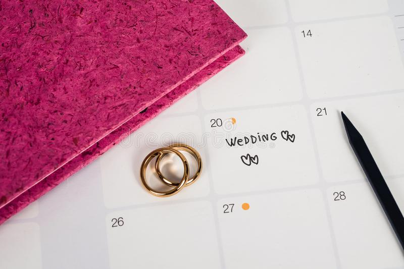 Word Wedding to Reminder Wedding day with Wedding ring on calendar planning stock photo