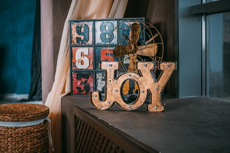 Word joy of the wooden letters. wedding decor. wedding photoshoot.In the foreground a wooden inscription Joy. old funny royalty free stock photo