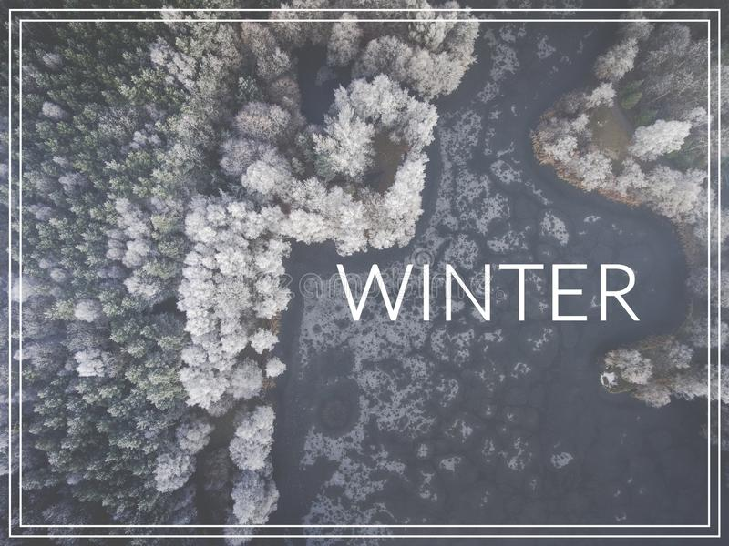 Word Winter over forest and lake from above. royalty free illustration