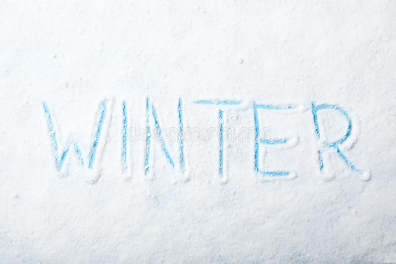 Word WINTER written in snow on color background stock photo