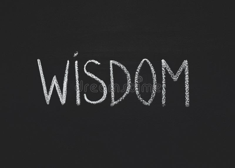 Word wisdom written on black chalkboard, copy space stock photos