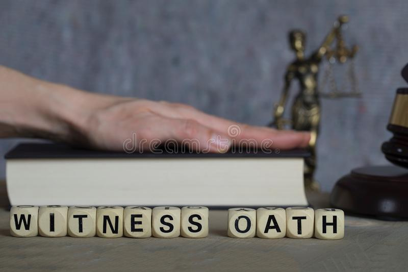Word WITNESS OATH composed of wooden letters. Statue of Themis,judge's gavel, bible in the background royalty free stock photos