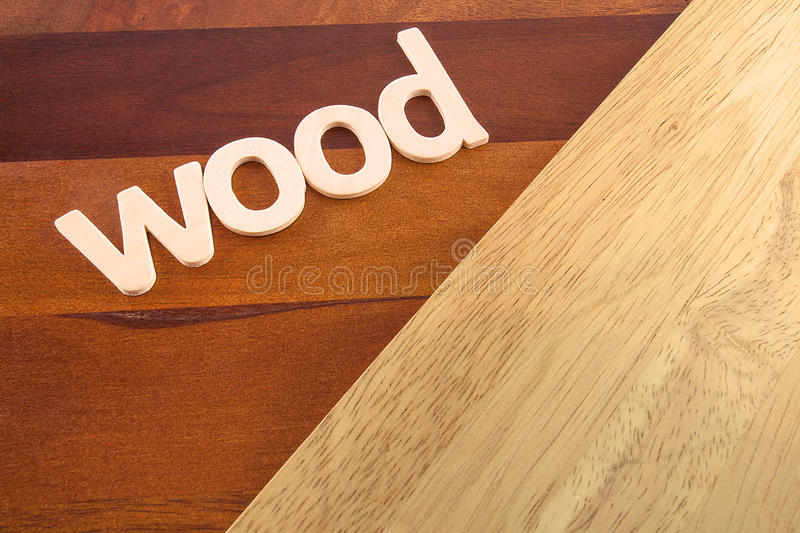 The Word Wood on Wooden Flooring. Red stained and natural wood flooring planks and the word wood in wooden letters royalty free stock images