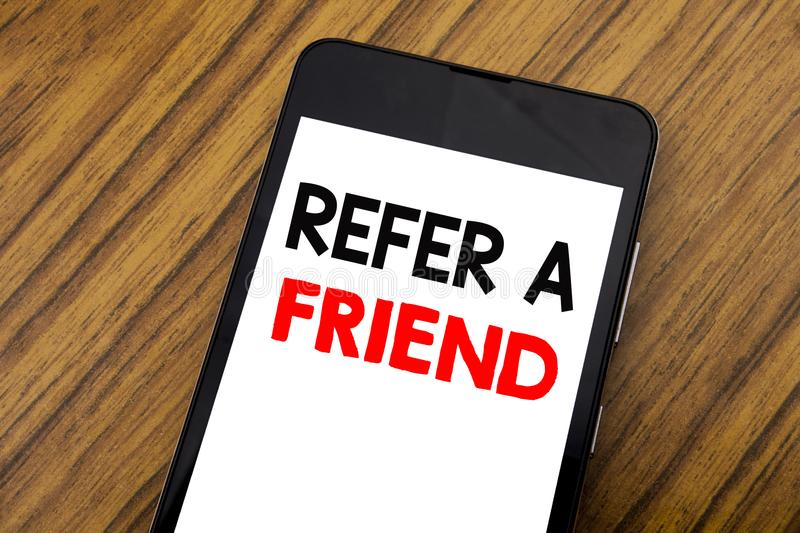 Word, writing handwriting Refer A Friend. Business concept for Referral Marketing Written on mobile phone cellphone, wooden backgr. Word, writing handwriting stock images