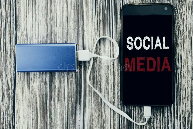 Word, writing Social Media. Business concept for Community Social Media written on mobile cell phone mobile and power-bank charger. Word, writing Social Media stock photos