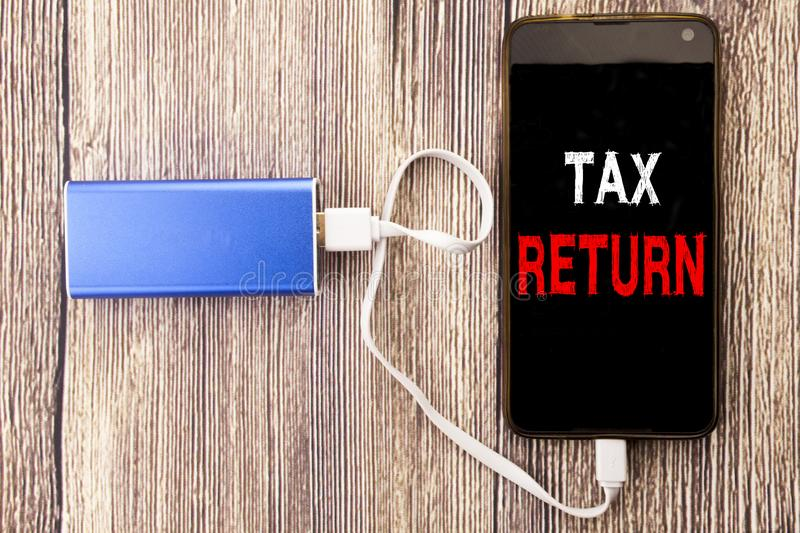 Word, writing Tax Return. Business concept for Accounting Money Return written on mobile cell phone mobile and power-bank charger. Word, writing Tax Return royalty free stock photos