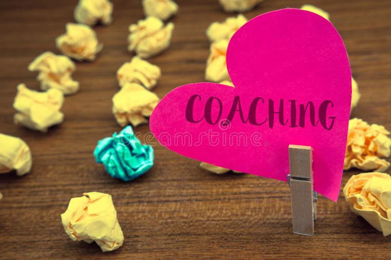 Word writing text Coaching. Business concept for Prepare Enlightened Cultivate Sharpening Encourage Strenghten Clothespin holding. Pink heart paper crumpled royalty free stock photography