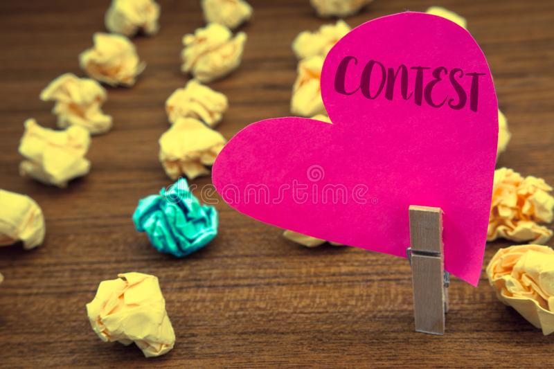 Word writing text Contest. Business concept for Game Tournament Competition Event Trial Conquest Battle Struggle Clothespin holdin. G pink heart paper crumpled stock images
