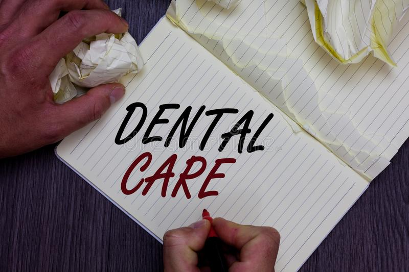 Word writing text Dental Care. Business concept for maintenance of healthy teeth or to keep it clean for future Man holding marker. Notebook crumpled papers stock photo