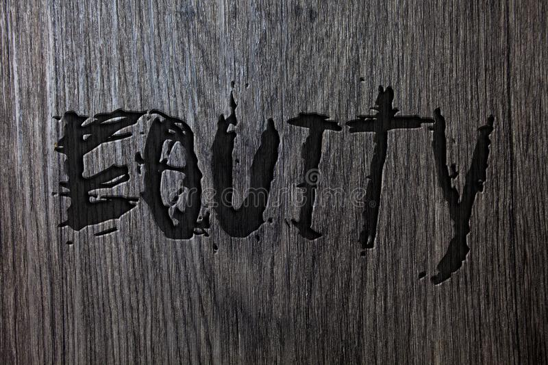 Word writing text Equity. Business concept for Value of a company divided into equal parts owned by shareholders Wooden wood backg. Round black engraved letters royalty free stock image
