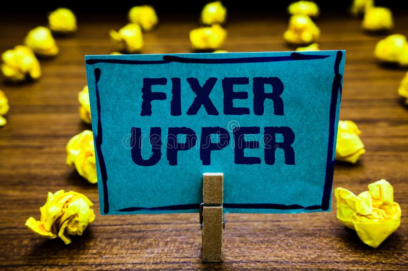 Word writing text Fixer Upper. Business concept for house in need of repairs used chiefly connection with purchase Clothespin hold. Ing blue paper note crumpled stock images