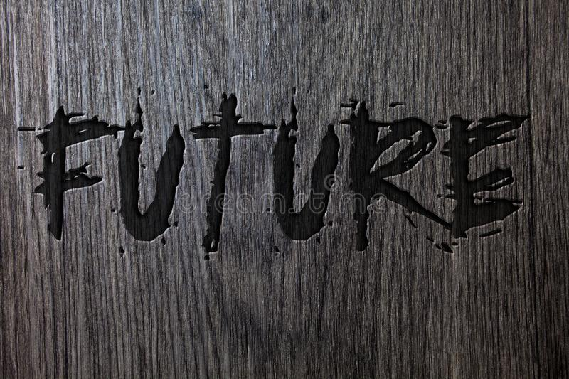Word writing text Future. Business concept for Period of time following the present moment Events that will happen Wooden wood bac. Kground black engraved royalty free stock photos