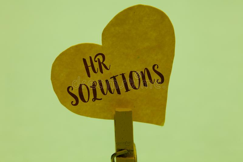 Word writing text Hr Solutions. Business concept for Outsourced Human resources consultancy and support Experts Clothespin holding. Yellow paper heart important stock photos