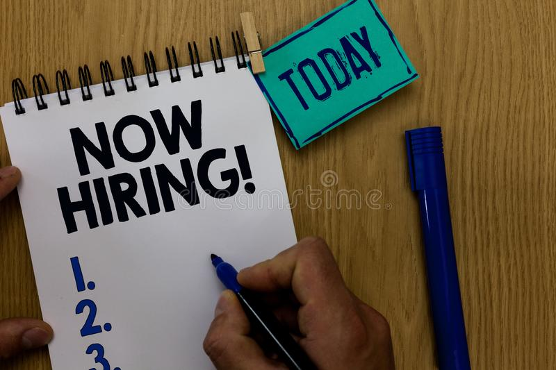 Word writing text Now Hiring. Business concept for announcing that certain company seeking for new talents Man holding marker note. Book clothespin reminder stock photography
