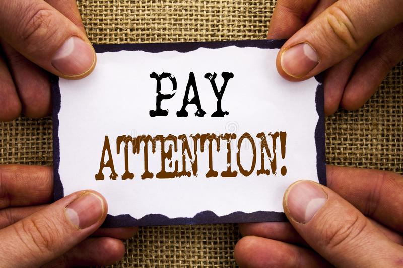 Word, writing, text Pay Attention. Conceptual photo Be Careful Beware Mindful Alarm written on Sticky Note Paper Holding Hand wit. Word, writing, text Pay stock photos