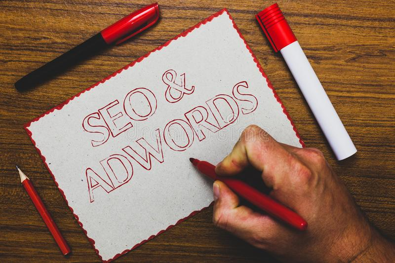 Word writing text Seo and Adwords. Business concept for Pay per click Digital marketing Google Adsense Man hand holding marker not. Ebook paper expressing ideas royalty free stock image