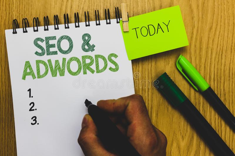 Word writing text Seo and Adwords. Business concept for Pay per click Digital marketing Google Adsense Man holding marker notebook. Clothespin reminder wooden royalty free stock image