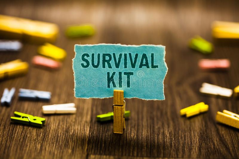 Word writing text Survival Kit. Business concept for Emergency Equipment Collection of items to help someone Clothespin holding bl. Ue paper note reminder stock image
