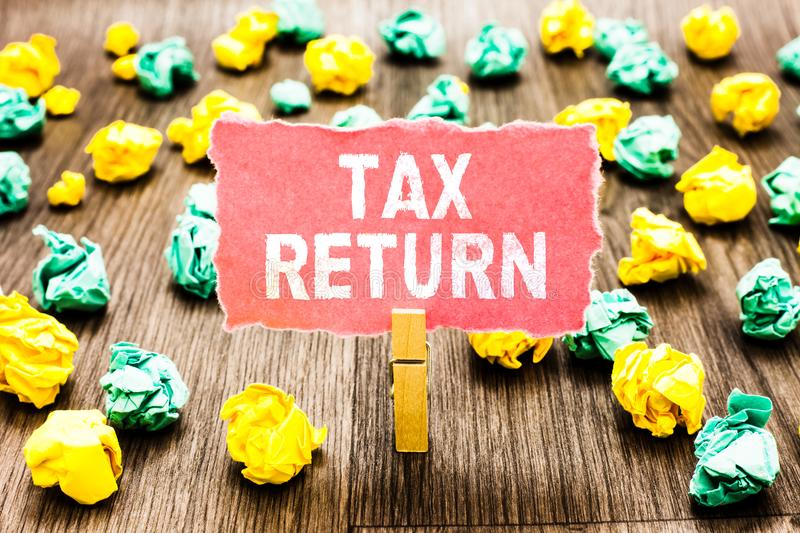 Word writing text Tax Return. Business concept for which taxpayer makes annual statement of income circumstances Clothespin holdin. G pink note paper crumpled royalty free stock photos