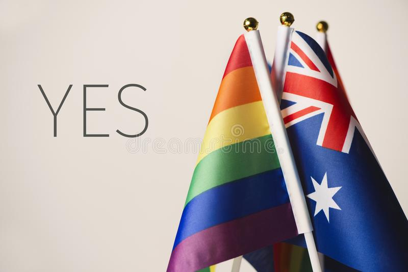 Word yes and australian and rainbow flags. Closeup of an australian flag and some rainbow flags, and the word yes, depicting the support to the same-sex union in stock photography