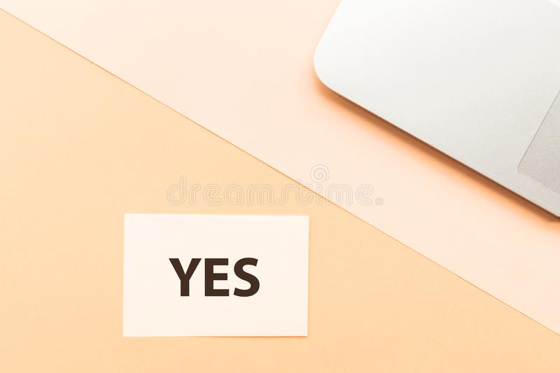 Word Yes and laptop on orange background. Creative minimalism chancery concept. Top view, flat lay, mockup. royalty free stock image