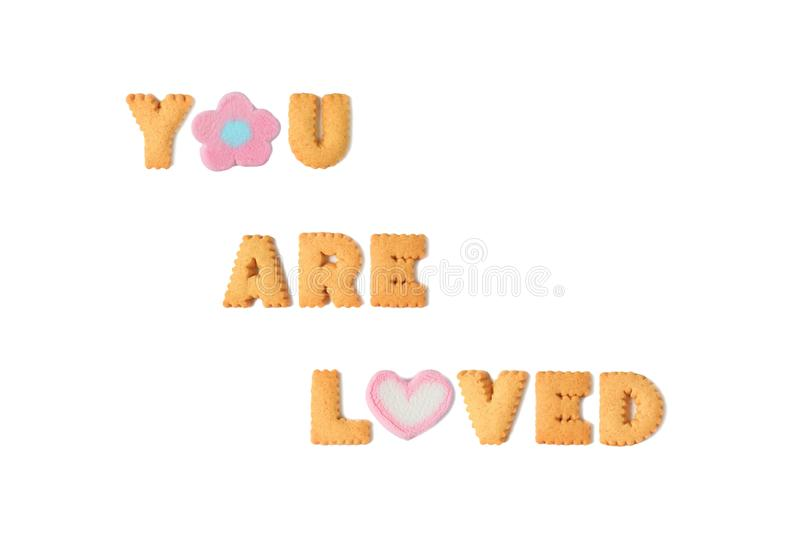 The word YOU ARE LOVED spelled with alphabet shaped cookies and marshmallow candies on white background royalty free stock photos