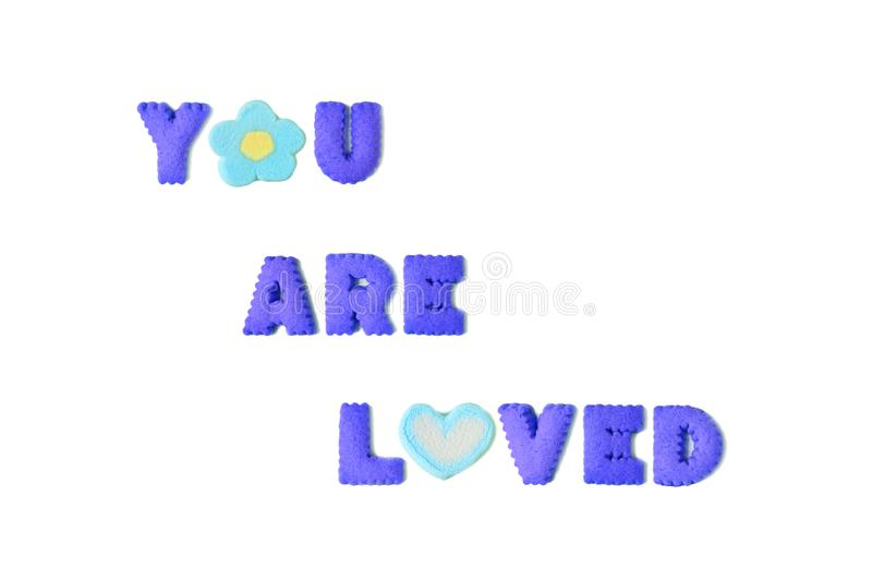 The word YOU ARE LOVED spelled with vivid blue alphabet shaped cookies and marshmallow candies. On white background, art, artistic, beautiful, biscuits, candy stock photos