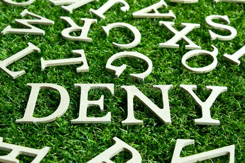 Wording deny on artificial green grass. With another english alphabet background royalty free stock photos