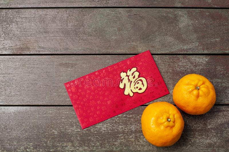 Wording of happiness on the red envelop with tangerines. Wording of happiness embroidered on the red envelop with two tangerines, placed on a wooden table stock photo