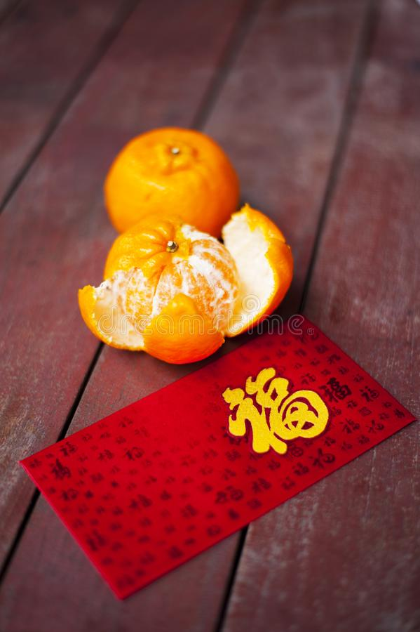 Wording of happiness on the red packet with tangerines. Wording of happiness embroidered on the red envelop with two tangerines, placed on a wooden table stock photos
