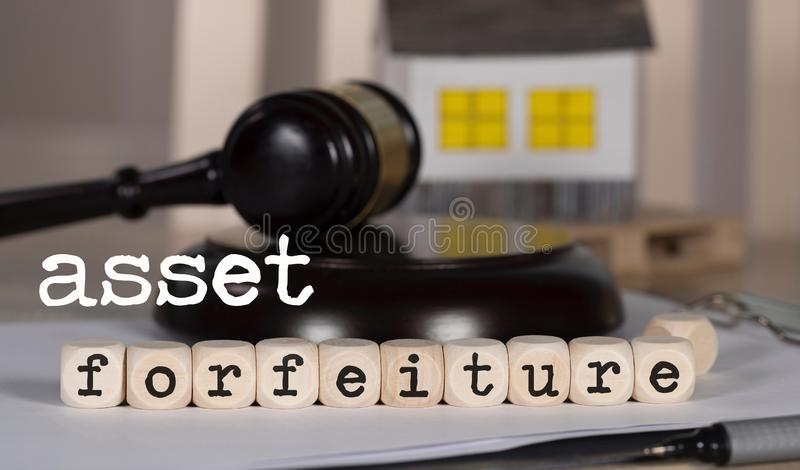 Words  ASSET FORFEITURE composed of wooden dices. Auction gavel on the table in the background. Closeup, seizure, confiscation, paper, house, real, estate stock images
