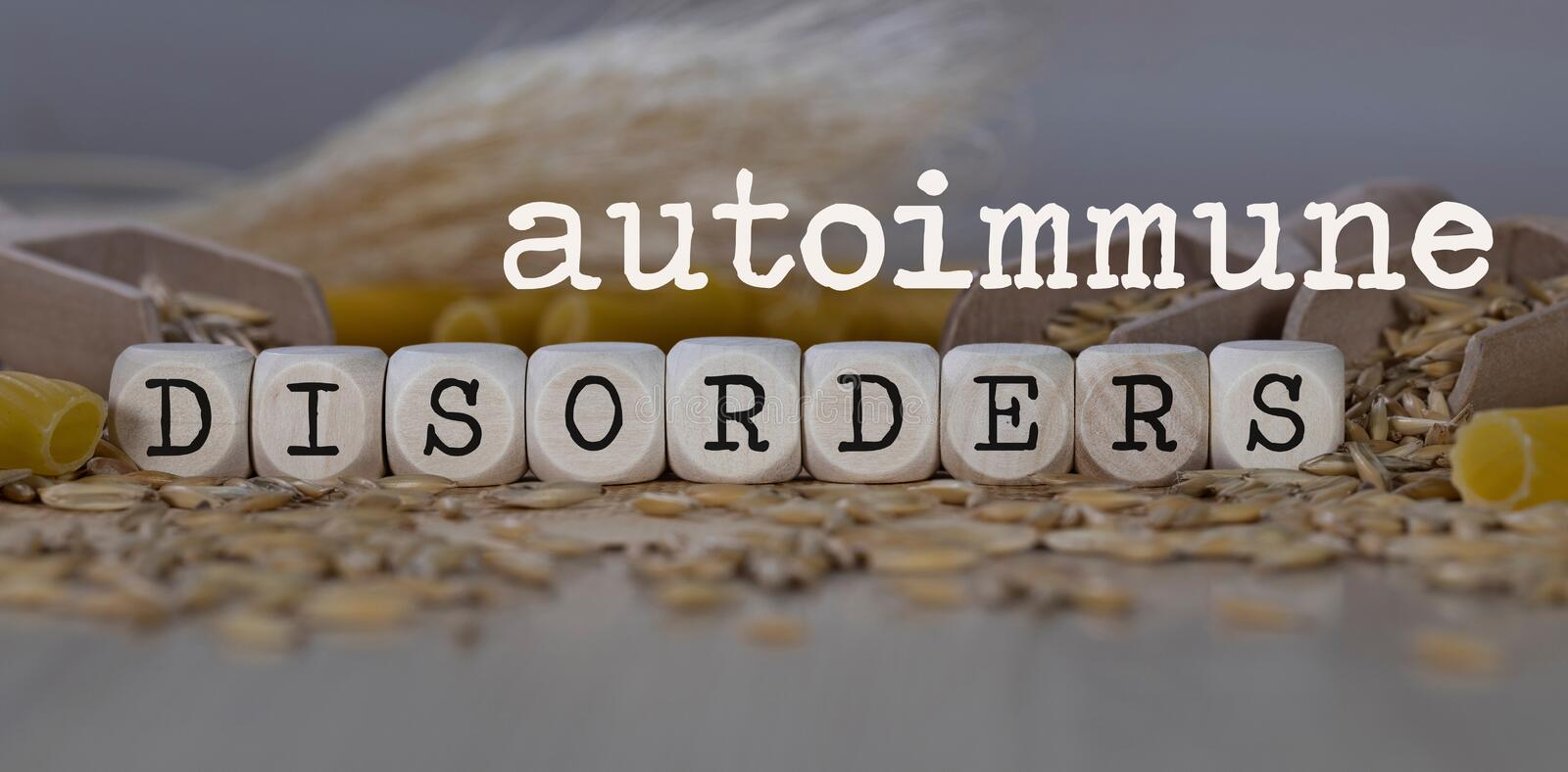 Words AUTOIMMUNE DISORDERS  composed of wooden dices. Rye grains in the background. Closeup, allergen, allergy, cereals, celiac, disease, gluten, intolerance stock photo