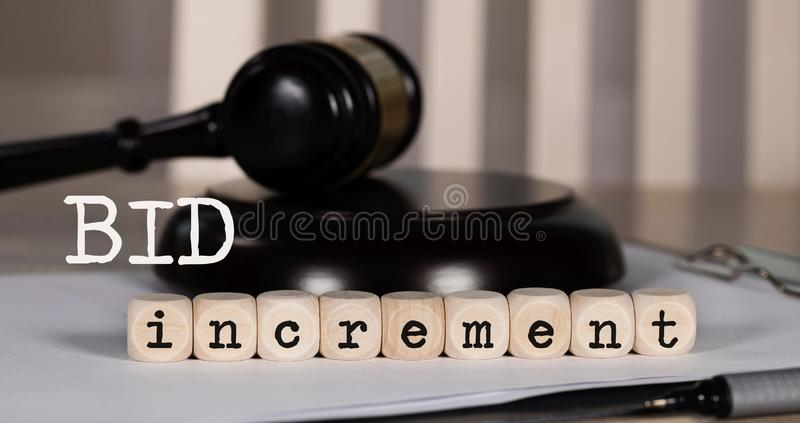 Words BID INCREMENT composed of wooden dices. Auction gavel on the table in the background. Closeup, auctioneer, increasing, bidding, business, buying, debts royalty free stock image