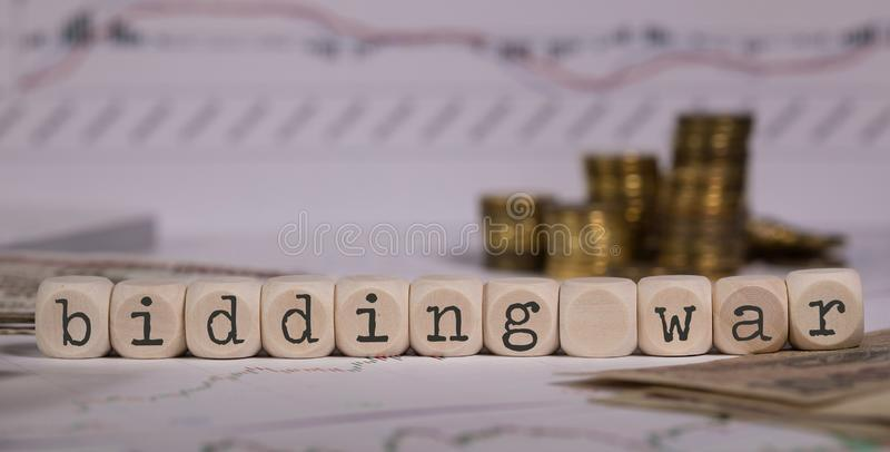Words BIDDING WAR composed of wooden letter. Stacks of coins in the background. Closeup royalty free stock photography