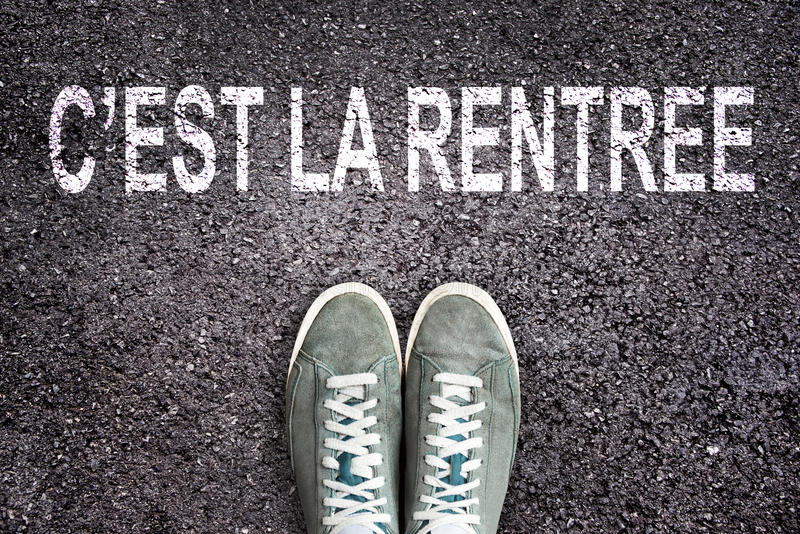 Words C`est la rentree meaning back to school written on asphalt road with sneakers shoes, high school and college con. Words C`est la rentree meaning back to stock photos