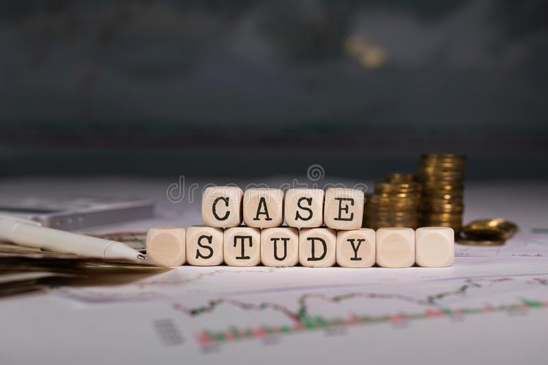 Words CASE STUDY composed of wooden letter. Stacks of coins in the background royalty free stock photography