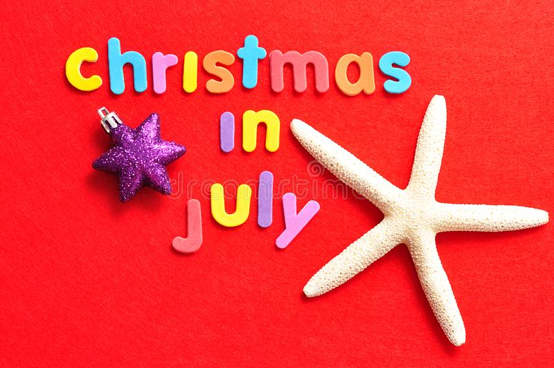 The words christmas in July on a red background with a starfish and a star shape bauble stock photos